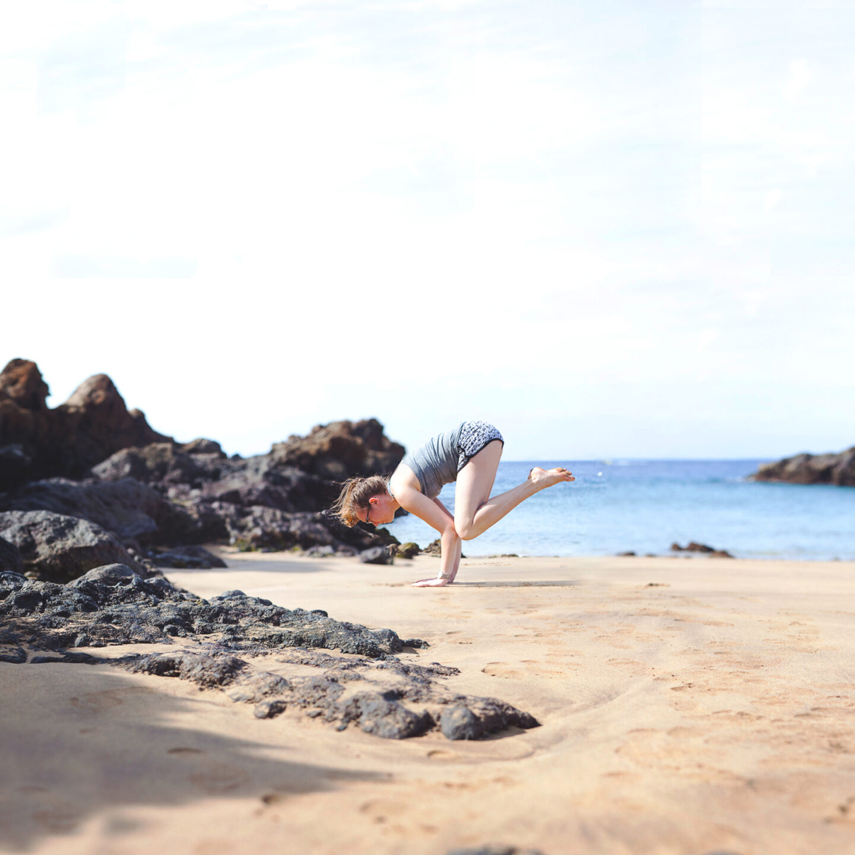Girl doing crow pose on beach.