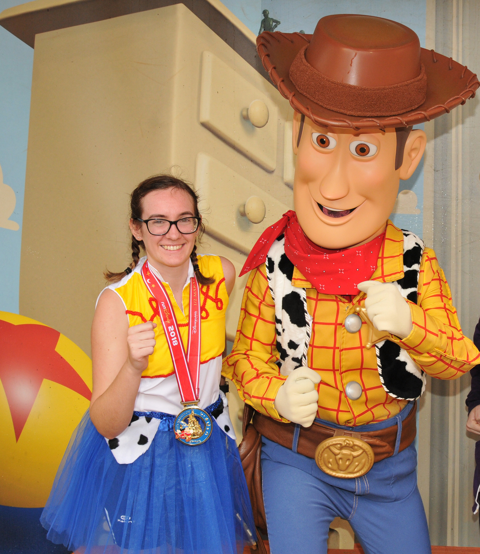 Girl in Jessie running costume posing with Woody character from Toy Story.