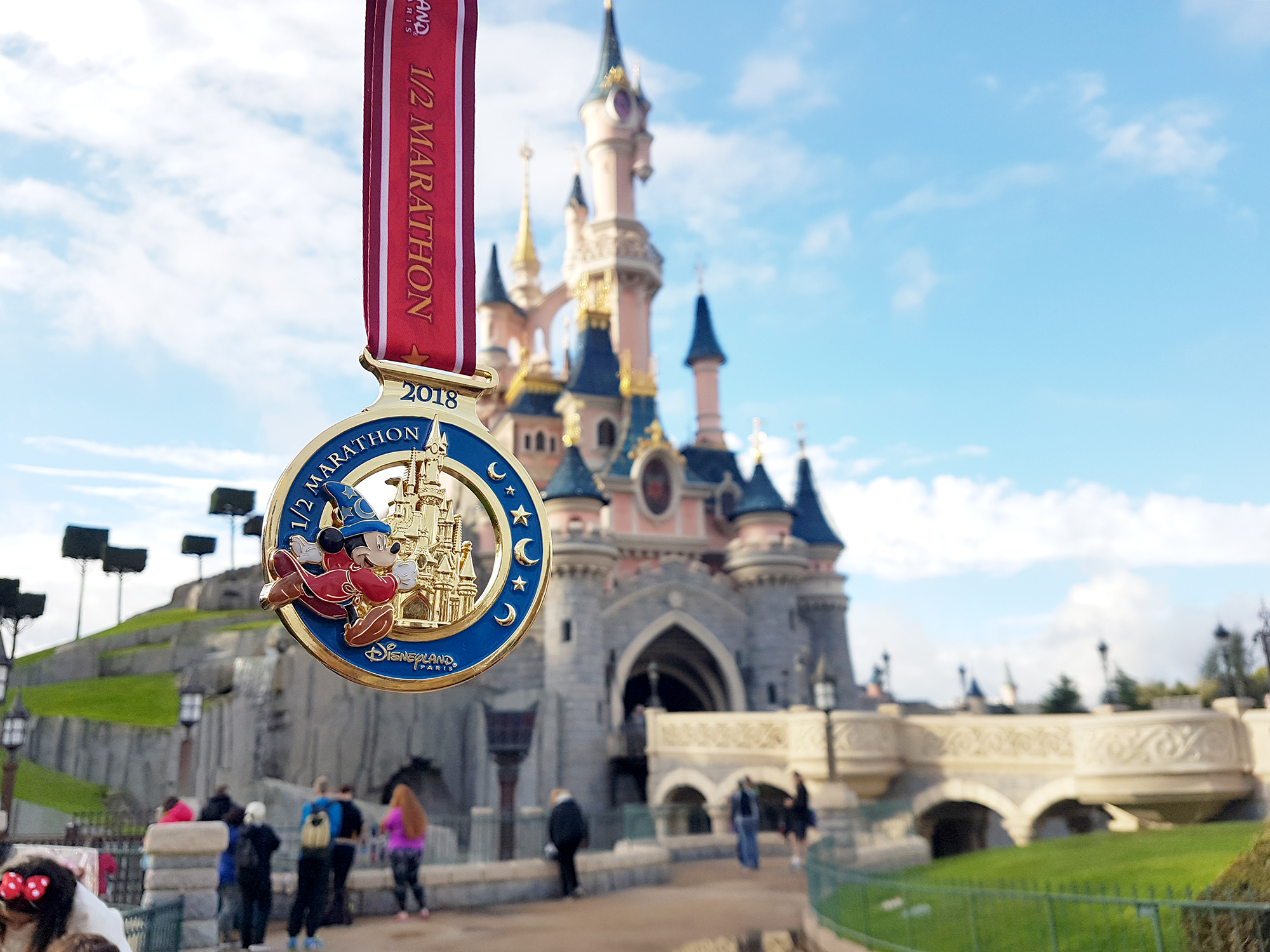 Disneyland Paris Half Marathon medal in front of the Castle. | 4 Things to Think About When Doing a Race Abroad