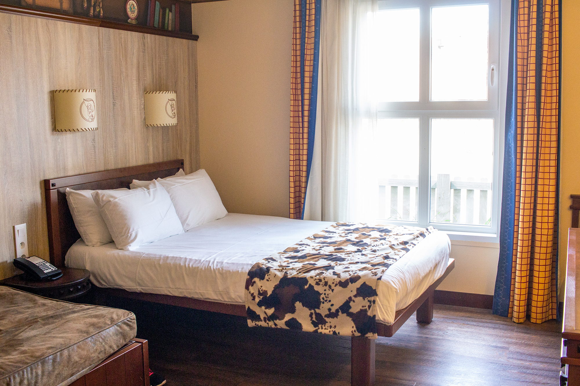 Hotel room bed with cow print furnishings, and curtains with yellow checked fabric | Staying at Hotel Cheyenne in Disneyland Paris