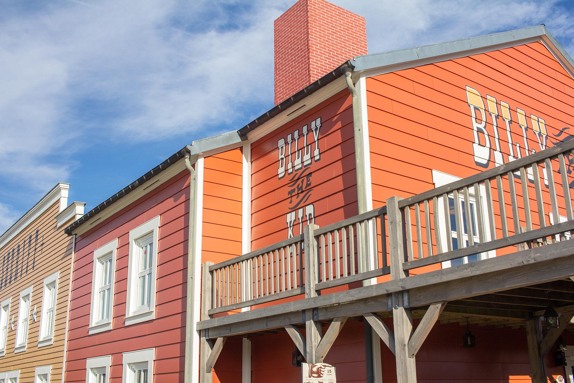 Orange building with Billy the Kid written on it. | Staying at Hotel Cheyenne in Disneyland Paris