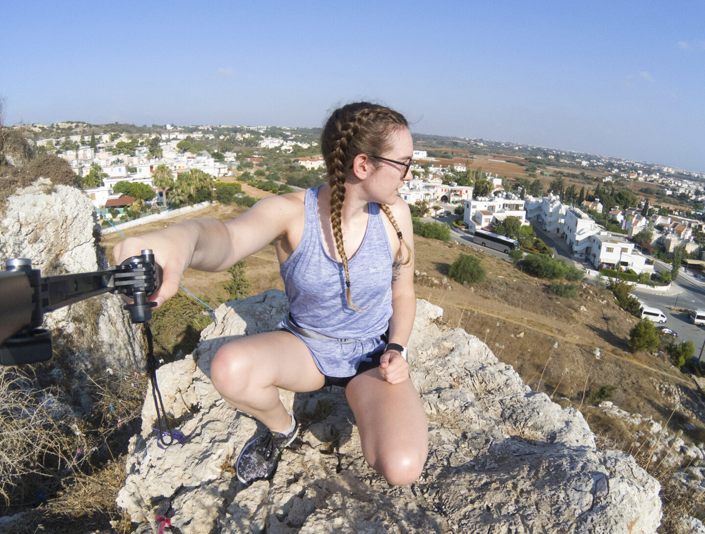 Girl on top of hill taking photo with selfie stick. | Tips For Taking Photos Of Yourself Whilst Travelling Solo