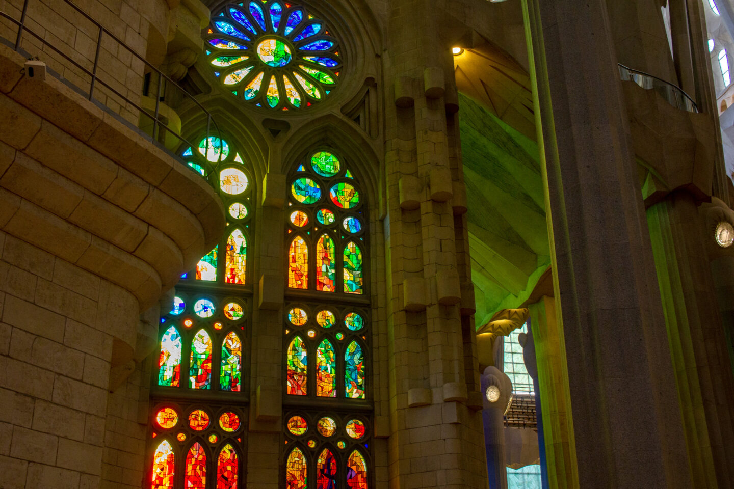 Stained glass window reflecting reds and greens.