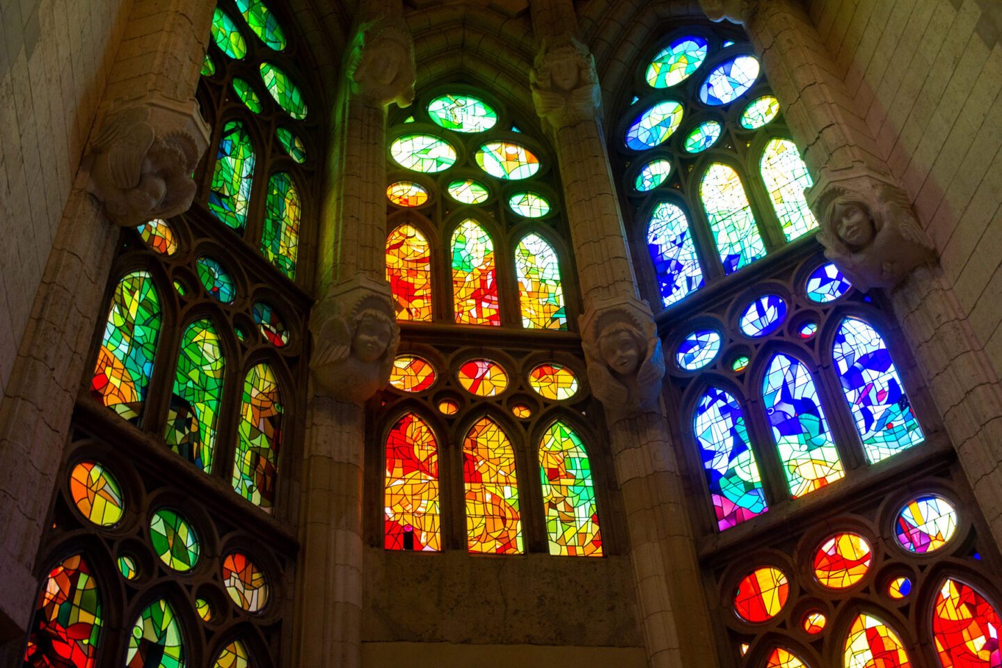 Stained glass windows showing greens, reds and blues.