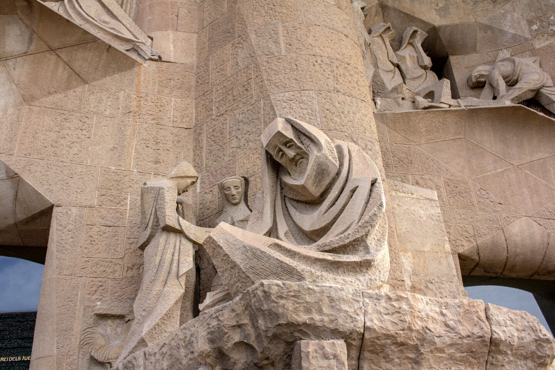 Statues outside the Sagrada Familia, a man sitting down.