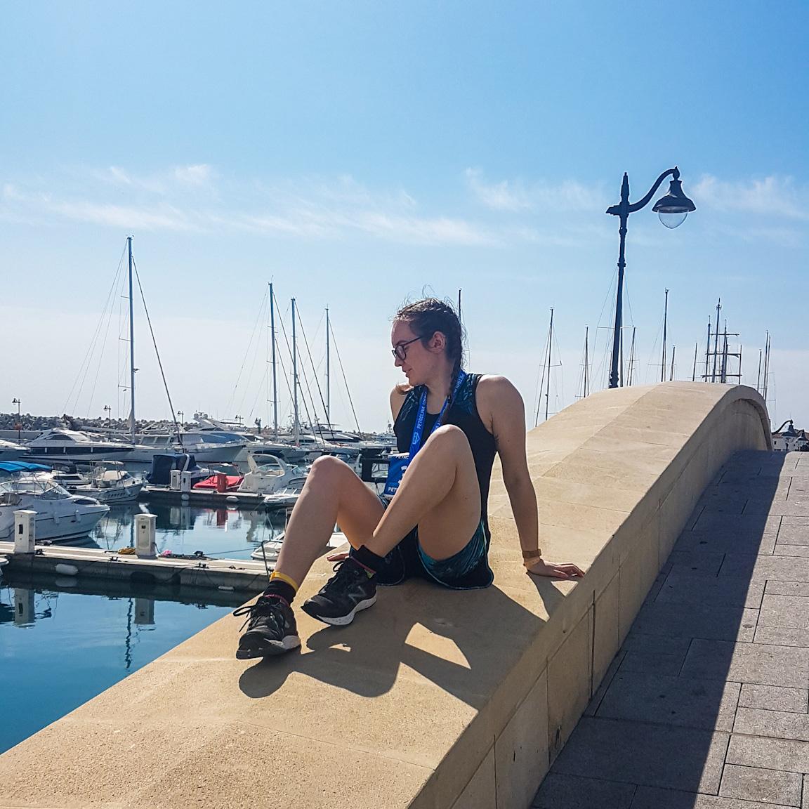 Girl sat on bridge at Limassol Marina.