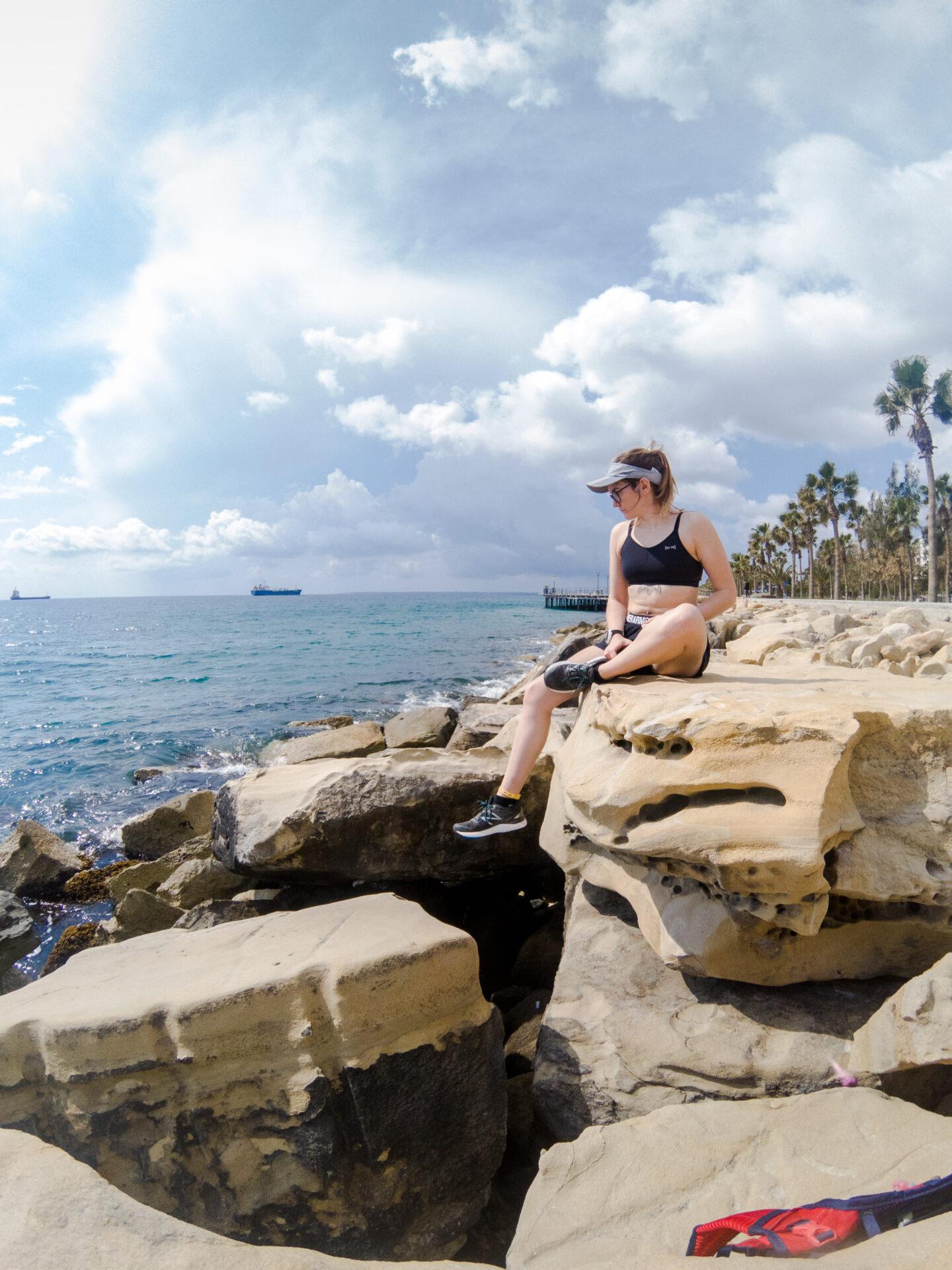 Girl sat in running gear on beach rocks.