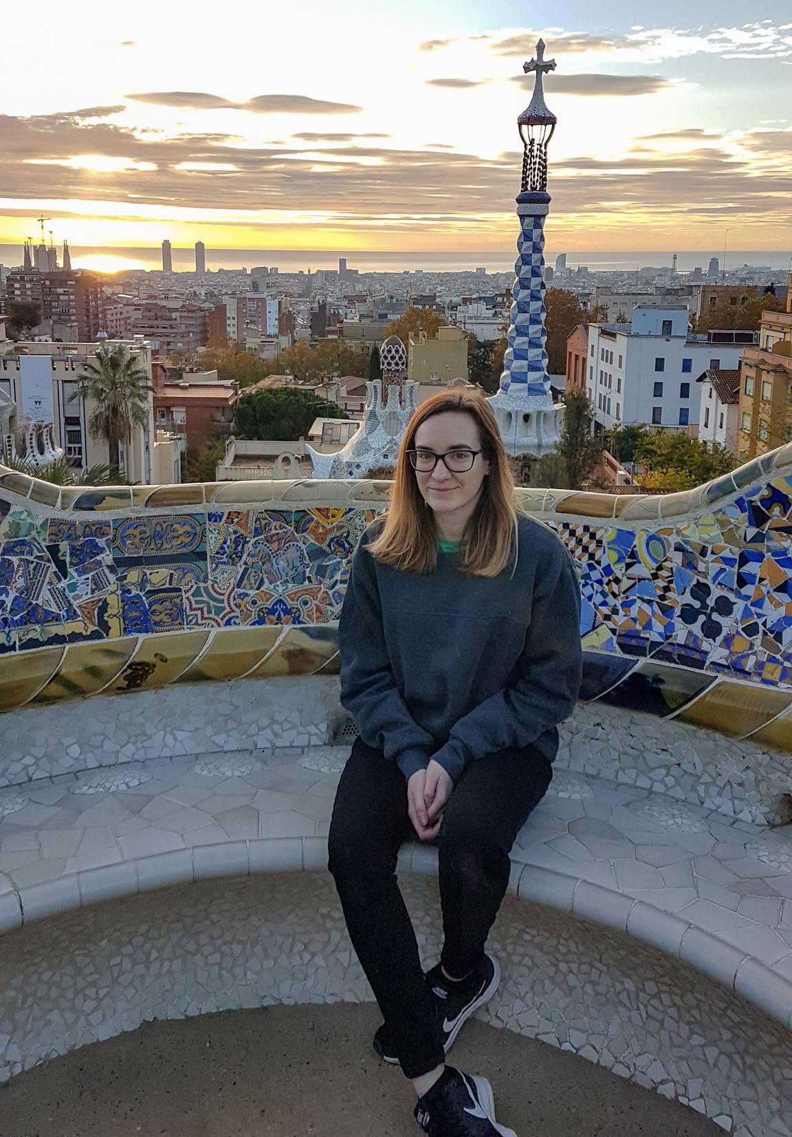 Girl sat in Park Guell, Barcelona with sunrise behind.