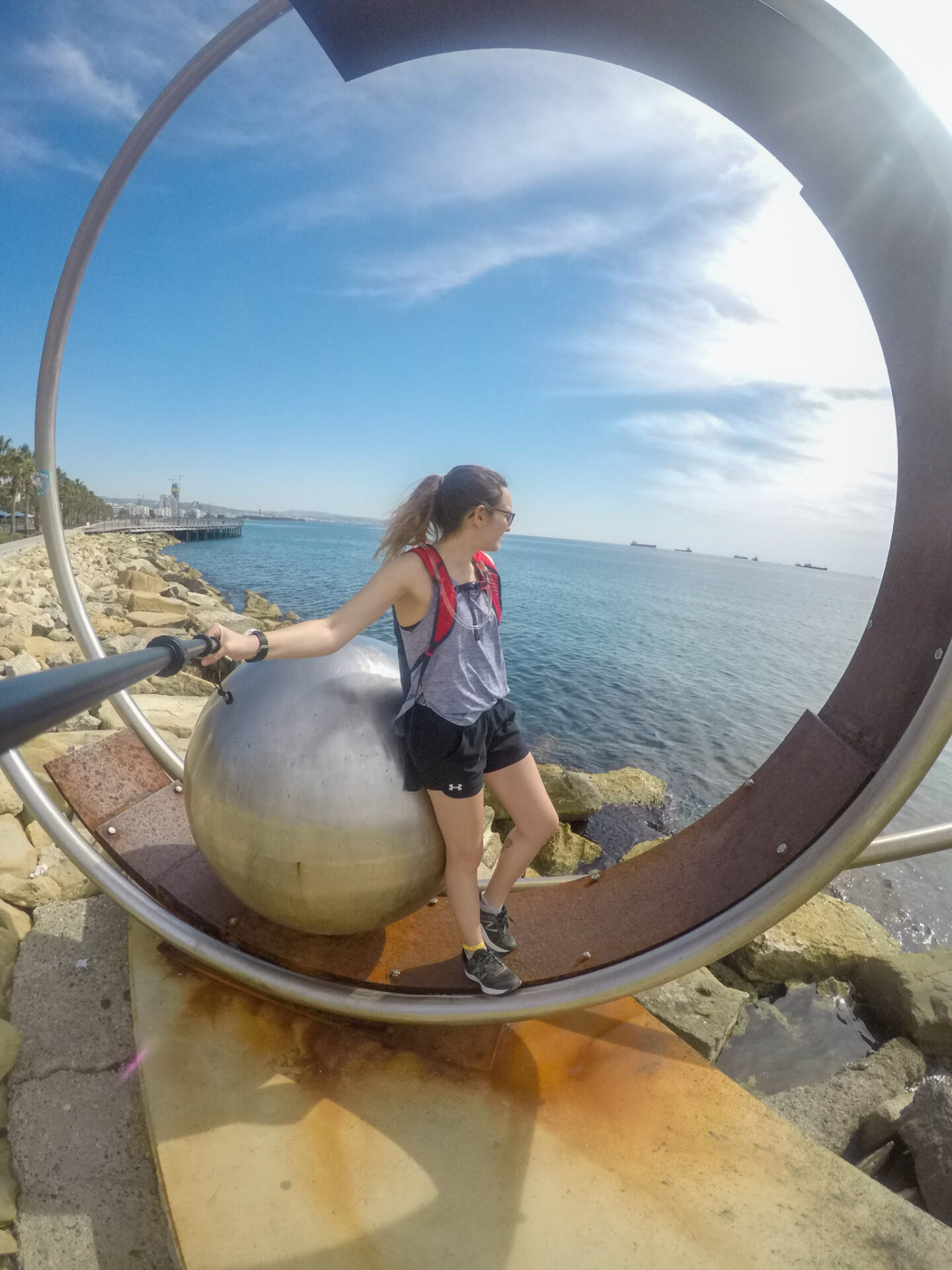 Girl on beach in limassol in circle statue.